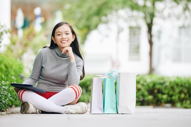 Feliz sorridente adolescente asiática sentada na estrada ao lado de sacolas de compras com um tablet digital nas mãos