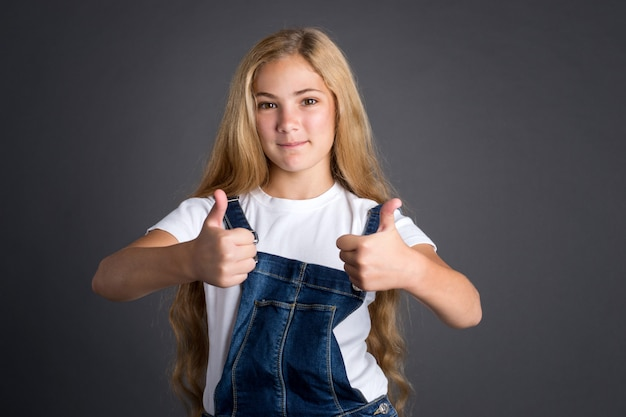 Feliz sorridente adolescente com cabelos longos dá polegares para cima gesto.