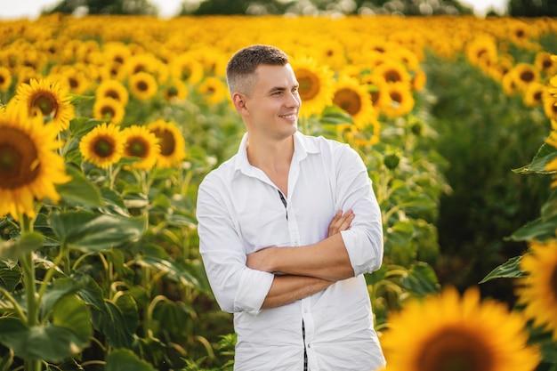 Feliz sorridente agricultor em pé orgulhoso na frente de seu campo de girassóis