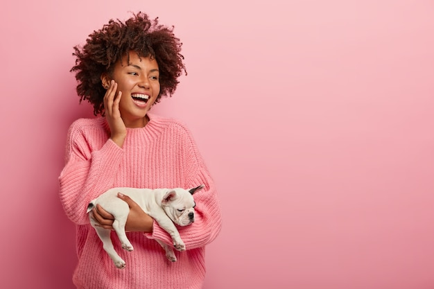 Feliz sorridente alegre mulher de pele escura carrega um cachorrinho de bulldog francês adormecido, usa um macacão rosa, focado à parte, estando em alto astral, isolado sobre uma parede rosa. monocromático. conceito de animais de estimação