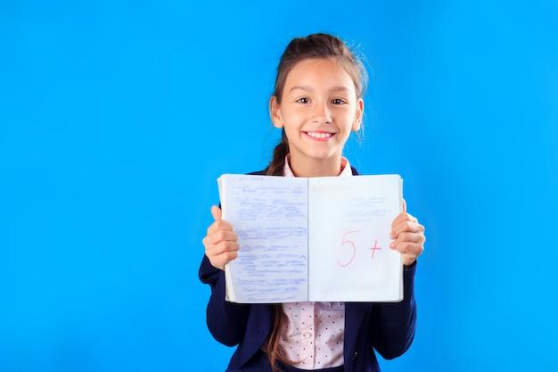 Feliz sorridente colegial de uniforme, segurando e mostrando o notebook com excelentes resultados de teste ou exame