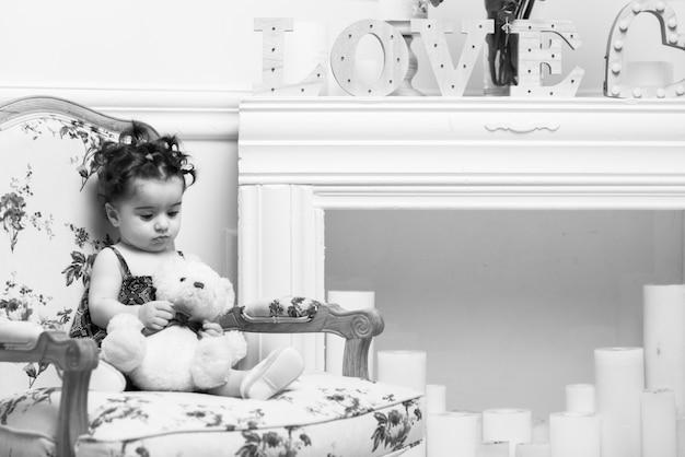 Feliz sorridente doce menina sentada na poltrona