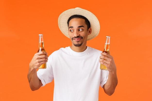 Feliz, sorridente e alegre cara caucasiano de chapéu relaxante durante a viagem país tropical, esfriando-se com bebida saborosa fria, segurando duas garrafas de cerveja, parede laranja de pé