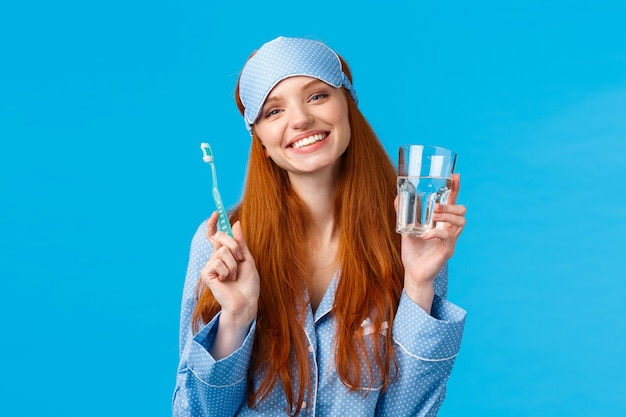 Feliz sorridente e despreocupada ruiva garota entusiasta na máscara do sono, pijama, segurando a água e a escova de dentes de vidro, cuidando da higiene bucal, rotina diária dental, parede azul