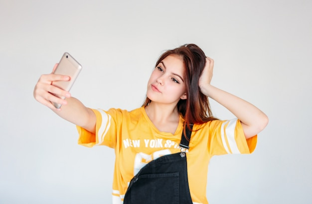 Feliz sorridente garota adolescente despreocupada, com cabelos longos escuros na camiseta amarela, fazendo selfie