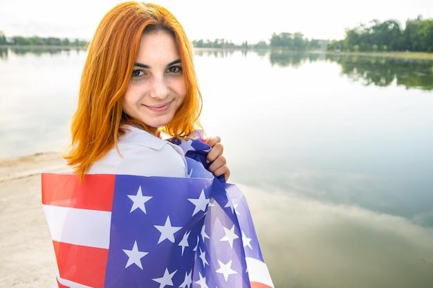 Feliz sorridente garota ruiva com a bandeira nacional dos eua nos ombros dela. mulher jovem positiva comemorando o dia da independência dos estados unidos.