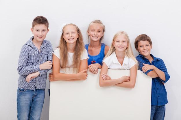 Feliz sorridente grupo de crianças, meninos e meninas, mostrando a placa