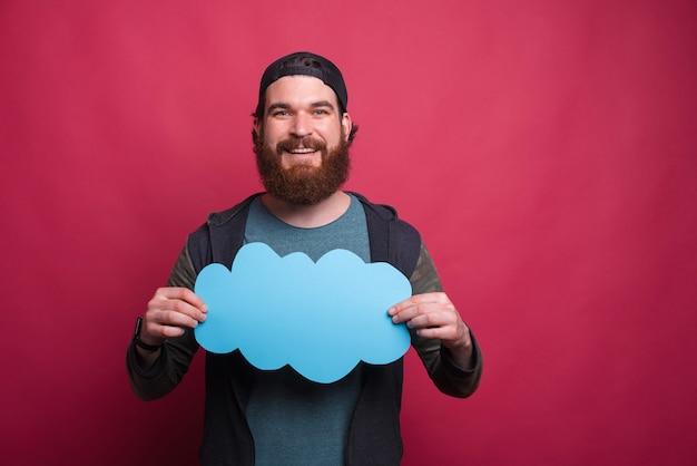 Feliz sorridente homem barbudo está segurando na frente de sua nuvem azul chesta