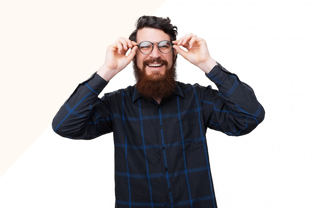 Feliz sorridente homem barbudo tocando armação de óculos