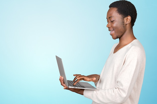 Feliz sorridente homem bonito com laptop