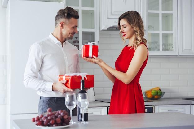 Feliz sorridente homem e mulher dando presentes uns aos outros de férias