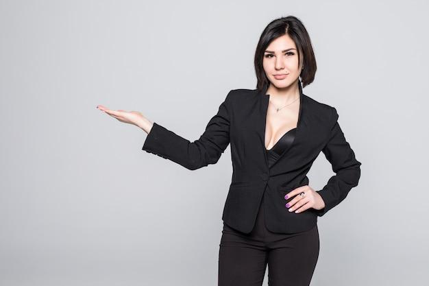 Feliz sorridente jovem bela empresária mostrando a área em branco para sinal ou copyspase, isolada no branco
