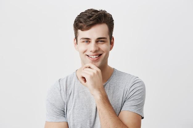 Feliz sorridente jovem demonstra emoções ou sentimentos positivos, tem penteado na moda, vestido casualmente, mantém a mão no queixo, fica contra a parede cinza com espaço de cópia de texto ou propaganda.