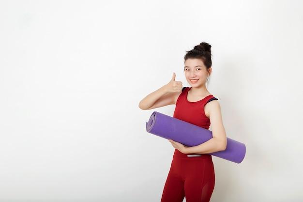 Feliz sorridente jovem esportista asiática fitness e yoga em roupas esportivas segurando o tapete, mostrando o polegar para cima e olhando a câmera