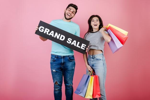 Feliz sorridente jovem homem e mulher pulando com sinal de grande venda e sacolas coloridas
