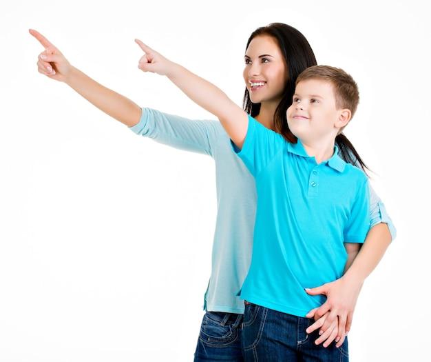 Feliz sorridente jovem mãe com filho apontando com os dedos. isolado no branco