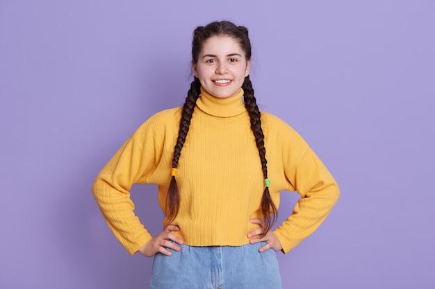 Feliz sorridente jovem mulher com cabelo longo bonito e tranças vestindo jeans e blusa amarela