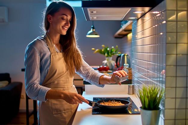 Feliz sorridente jovem mulher dona de casa cozinhando salgando e preparando comida em uma frigideira no fogão para o jantar na cozinha moderna de estilo loft