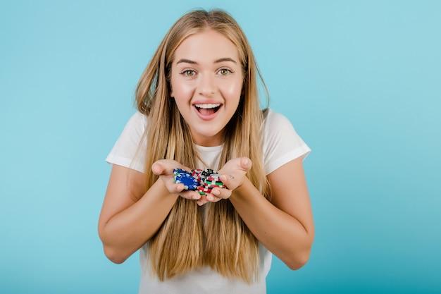 Feliz sorridente jovem mulher loira com fichas de poker nas mãos isoladas sobre azul
