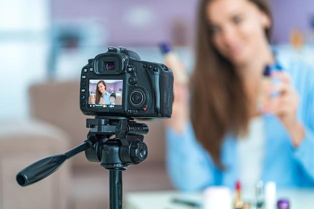Feliz sorridente jovem vídeo blogger durante a gravação de seu blog de beleza sobre maquiagem e cosméticos em casa. blogs e transmissão ao vivo com o público