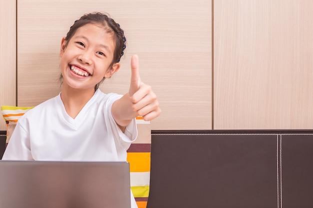 Feliz sorridente menina asiática usando computador notebook para estudar no quarto dela