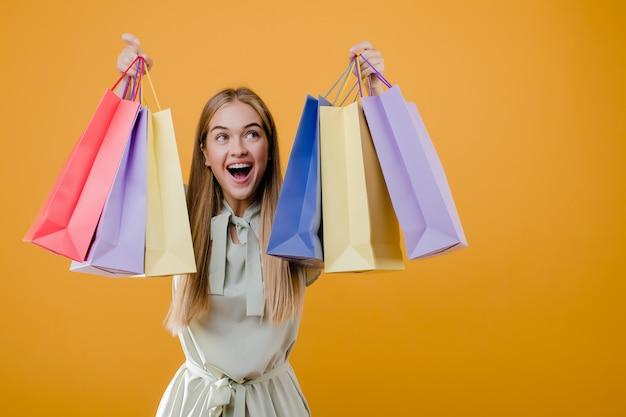 Feliz sorridente menina loira com sacolas coloridas isoladas sobre amarelo