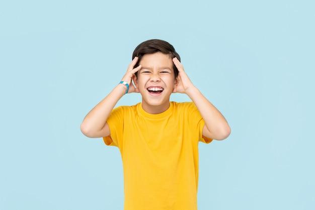 Feliz sorridente menino asiático com as mãos apertando a cabeça isolada na parede azul clara