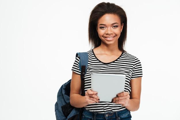 Feliz sorridente mulher adolescente africana com mochila usando tablet pc