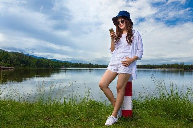 Feliz sorridente mulher asiática segurando e olhando para o telefone dela perto de um lago