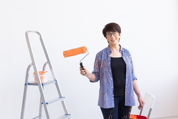 Feliz sorridente mulher de meia-idade pintando a parede interior da casa nova. redecoração, renovação
