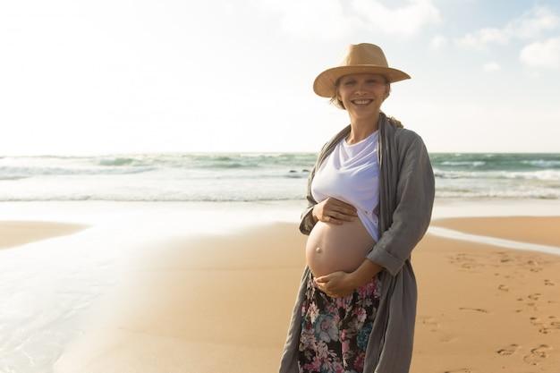 Feliz sorridente mulher grávida de mãos dadas na barriga