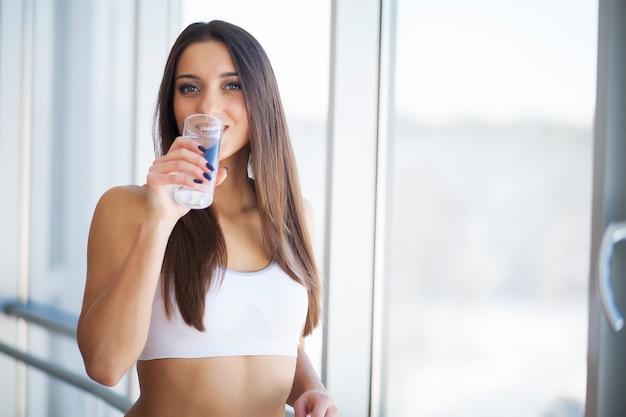 Feliz sorridente mulher jovem bebendo água