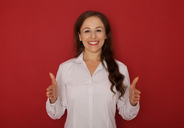 Feliz sorridente mulher jovem e bonita mostrando copyspace ou algo assim