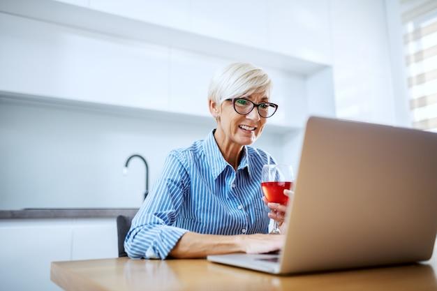 Feliz sorridente mulher loira sênior sentado à mesa de jantar, bebendo vinho tinto e tendo videochamada no laptop