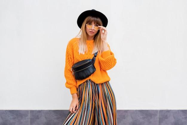 Feliz sorridente mulher morena em pé no branco na elegante camisola laranja e listra multicolorida culotte