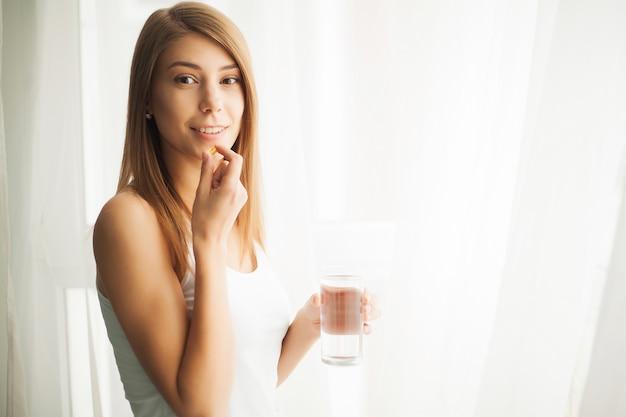 Feliz sorridente mulher positiva comendo a pílula e segurando o copo de água na mão, em sua casa