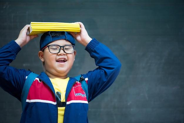 Feliz sorridente rapaz asiático em óculos está indo para a escola pela primeira vez
