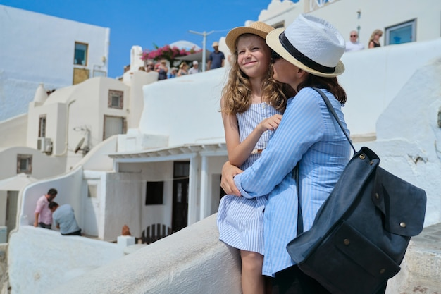 Feliz sorrindo abraçando a filha mãe e filho, apreciando a vista panorâmica da natureza e da arquitetura da ilha de santorini. férias de verão com a família