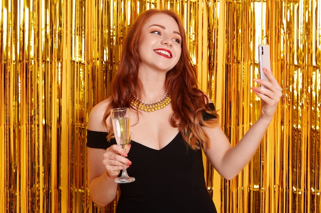 Feliz sorrindo com make posando contra ouropel dourado e fazendo selfie via telefone inteligente moderno, garota de vestido preto, senhora segurando um copo de vinho, comemorando o evento importante.