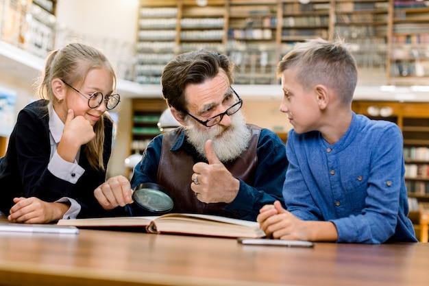 Feliz sorrindo crianças adolescentes com o avô lendo livro de história na biblioteca vintage