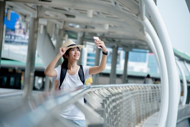 Feliz, sorrindo, estudante asiático, menina, com, mochila, em, cidade, fundo