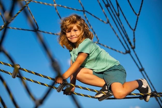 Feliz sorrindo fofo criança menino jogar barras de macaco na web em crianças de recreio ao ar livre em corda p ...