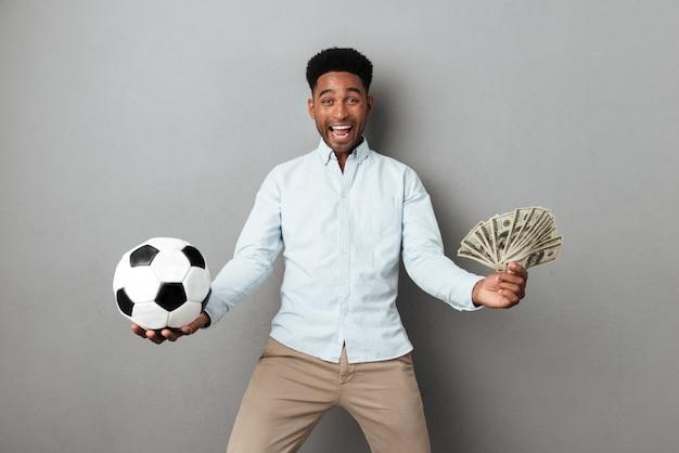 Feliz sorrindo homem africano segurando notas de futebol e dinheiro