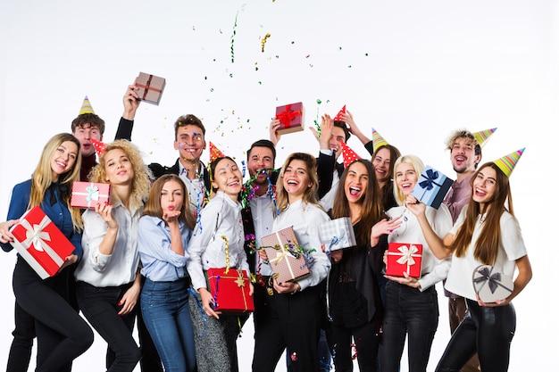 Feliz sorrindo jovens com caixas de presente e decorações para festas
