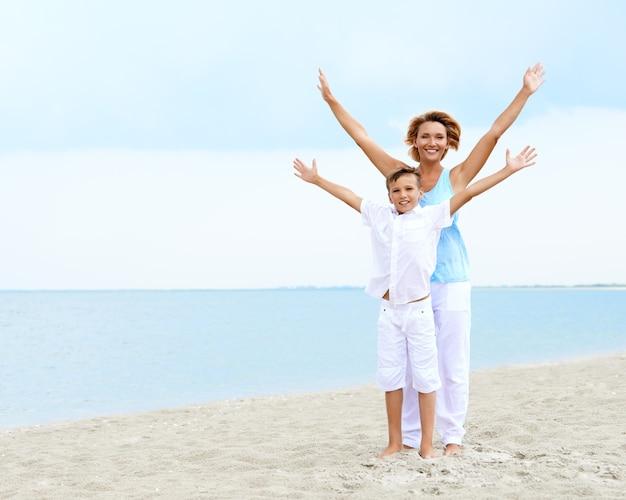 Feliz sorrindo mãe e filho em pé na praia com as mãos levantadas.