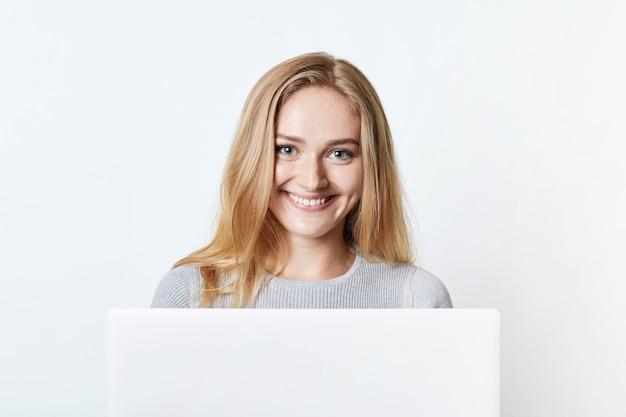 Feliz sorrindo mulher independente trabalha em casa, senta-se na frente do laptop aberto, goza de conexão de internet sem fio gratuita. adoráveis mensagens de adolescente com amigos, tem um sorriso agradável no rosto
