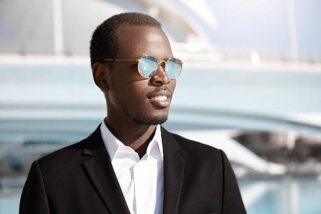 Feliz sucesso jovem empregado preto elegante roupa formal e óculos de sol olhando alegre, regozijando-se em seus objetivos de carreira