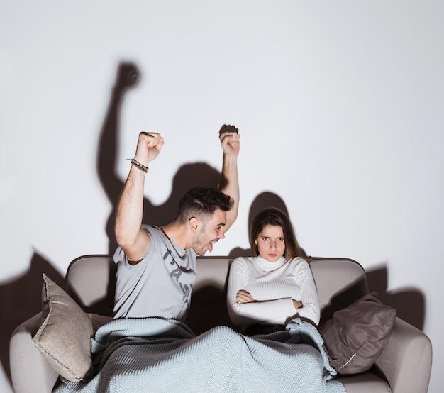 Feliz, sujeito, e, zangado, senhora, tv assistindo, ligado, sofá