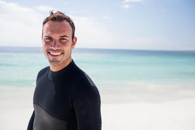 Feliz surfista em pé na praia