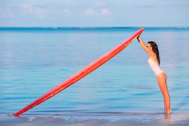 Feliz surfista linda na praia com sua prancha de surf